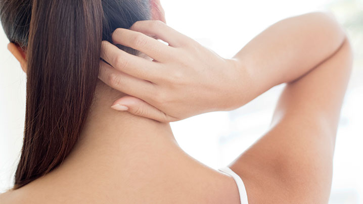 woman touching back of her neck